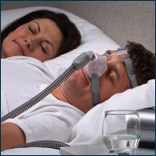 Man wearing CPAP Mask sleeping next to woman