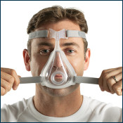 Man putting on Full Face CPAP mask