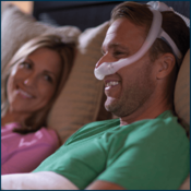 Man wearing CPAP Mask sitting next to woman