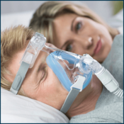 Man wearing Full Face CPAP mask sleeping next to woman