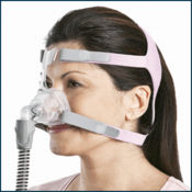 Woman wearing Nasal CPAP mask with pink headgear